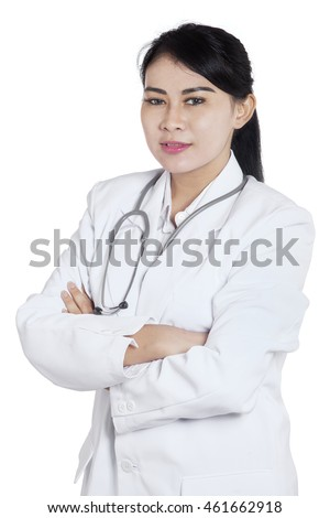 Portrait of a pretty female young doctor smiling at the camera with folded arms in the studio
