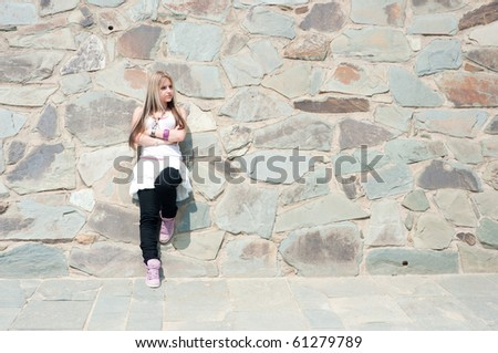 Portrait of a pretty girl at a stone wall