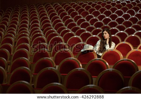 portrait of a pretty girl hipster in a movie theater wearing hat, dreaming alone - stock photo