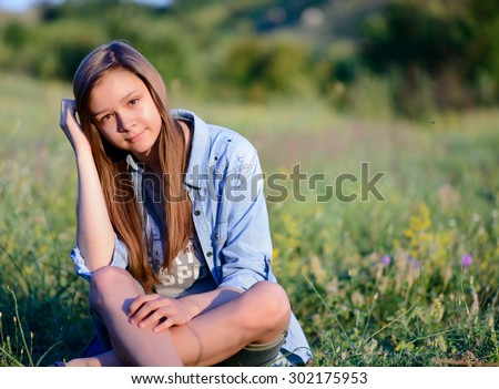 Portrait of a Pretty Girl Holding her Long Blond Hair While Sitting on Grasses with Legs Crossed and Looking at Camera