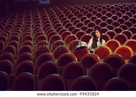 portrait of a pretty girl in a movie theater - stock photo