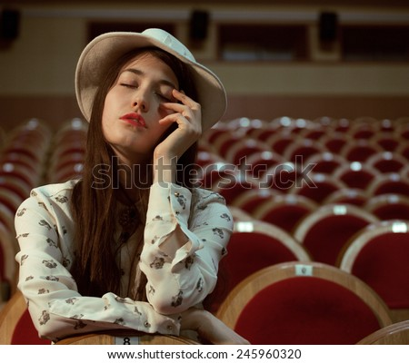 portrait of a pretty girl in a movie theater wearing hat, dreaming - stock photo