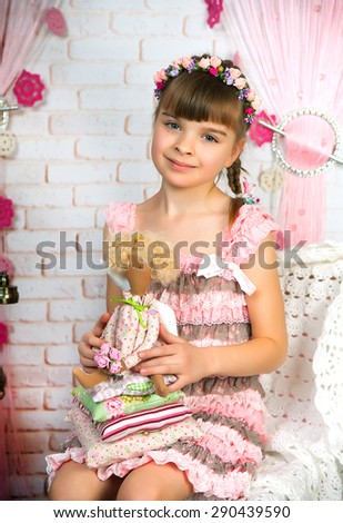 portrait of a pretty girl in a pink fishnet dress and a wreath with a doll in the scenery