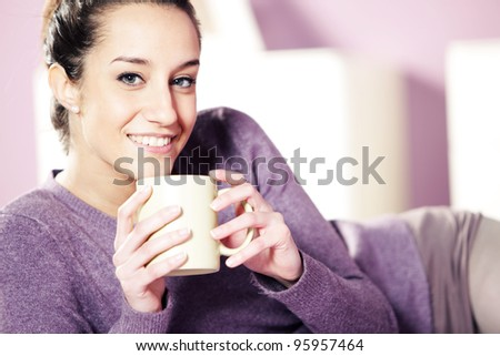 Portrait of a pretty happy young woman holding a cup of coffee in bed - stock photo