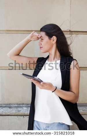 Portrait of a pretty latin woman holding hand near forehead looking for some street or direction in urban setting, stylish business female using digital tablet computer in the city walking - stock photo