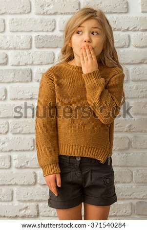 Portrait of a pretty little blonde girl showing emotions, covering her mouth and looking away while standing against white brick wall - stock photo