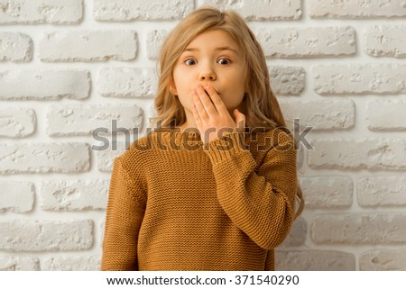 Portrait of a pretty little blonde girl showing emotions, covering her mouth and looking in camera while standing against white brick wall - stock photo