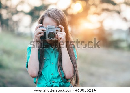 Portrait of a pretty little brunette girl smiling and holding a camera while standing in the woods - stock photo