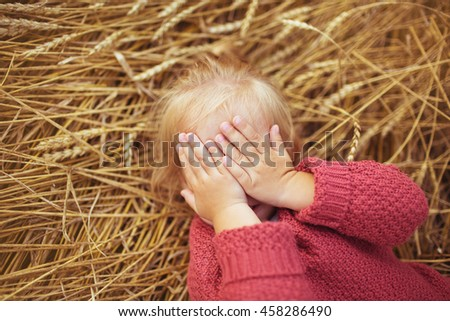 Portrait of a pretty little girl lies on a ears of wheat and closes his eyes - stock photo