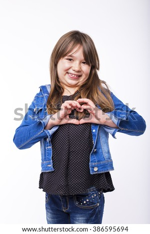 Portrait of a pretty little girl showing heart sign over white background