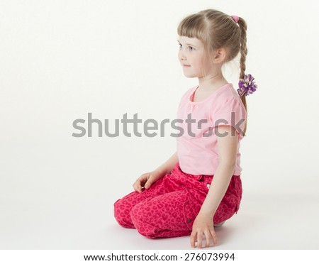 Portrait of a pretty little girl sitting on the floor, white background - stock photo