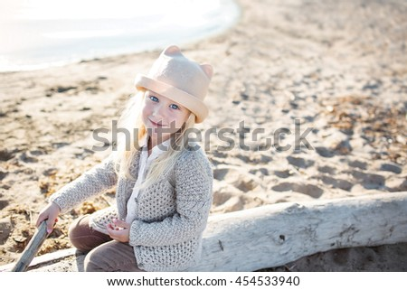 Portrait of a pretty little girl wit a light hat and knitted jacket on a beach - stock photo