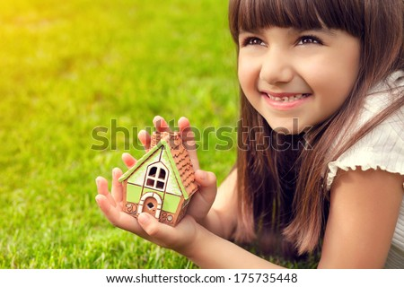 portrait of a pretty little girl with house in hand on a background of green grass - stock photo