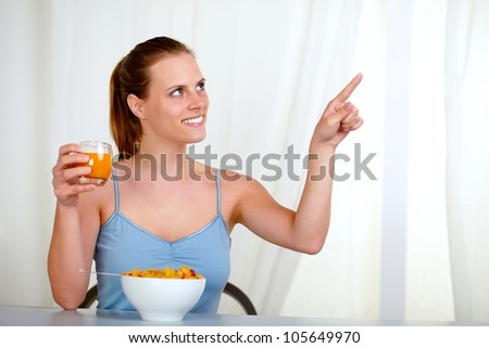 Portrait of a pretty lovely woman eating meal and pointing to the right at home indoor - stock photo