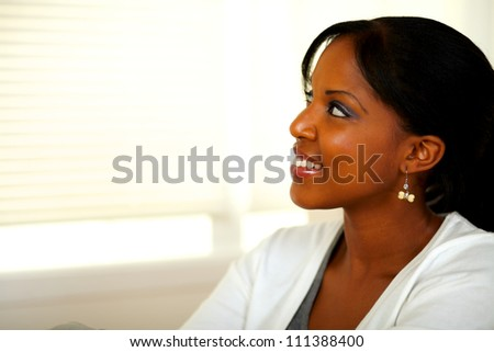 Portrait of a pretty lovely young woman looking at her right at home indoor. With copyspace