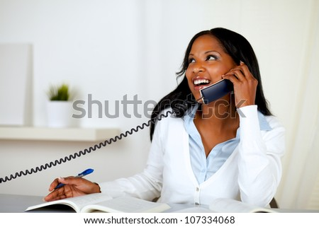 Portrait of a pretty lovely young woman smiling and looking up while is on phone at home indoor - stock photo