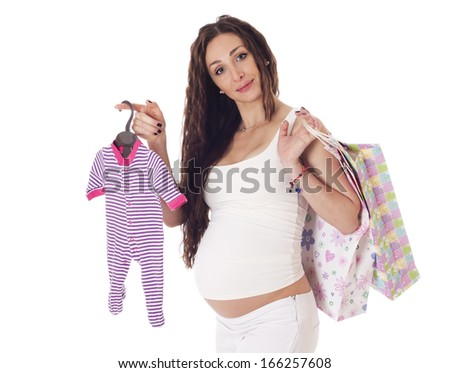 Portrait of a pretty middle aged pregnant woman with baby clothes and shopping bags over white background. - stock photo