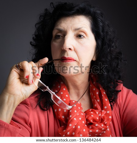 Portrait of a Pretty Older Woman Holding Reading Glasses and Looking away from the Camera - stock photo