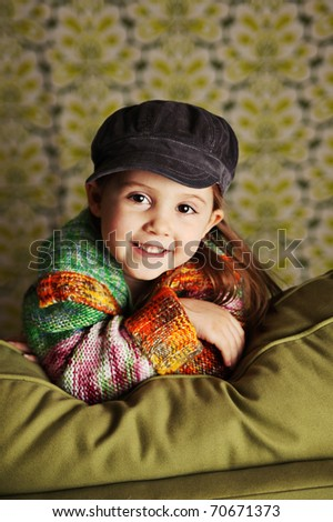 Portrait of a pretty preschool girl wearing a bright sweater and hat sitting on a green couch - stock photo