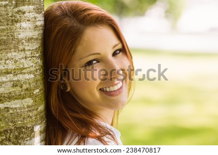 Portrait of a pretty redhead smiling against trunk in park