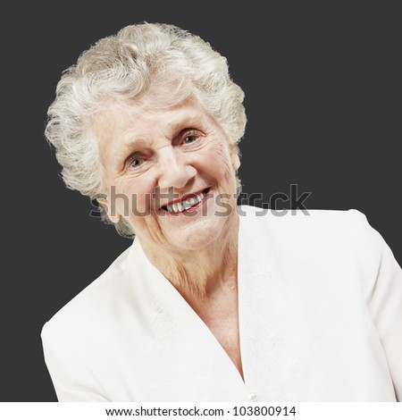 portrait of a pretty senior woman smiling against a black background - stock photo
