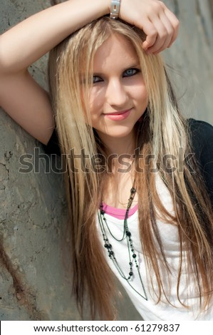 Portrait of a pretty smiling blond girl at a wall