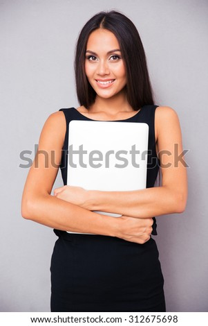 Portrait of a pretty smiling businesswoman holding laptop on gray background - stock photo