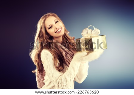 Portrait of a pretty smiling woman in warm clothing holds a gift box. - stock photo