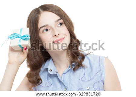 Portrait of a pretty teenage brunette girl posing holding a small present in her hand looking aside smiling, isolated on white background - stock photo