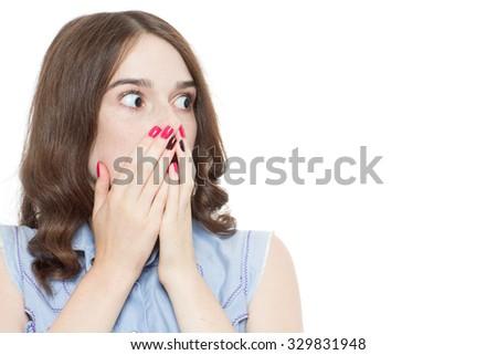 Portrait of a pretty teenage brunette girl posing holding hands near her face looking very surprised, isolated on white background - stock photo