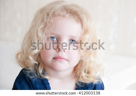 portrait of a pretty toddler with blue eyes and blonde curly hair - stock photo