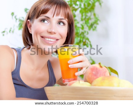 Portrait of a pretty woman holding glass with tasty juice, female sitting on the kitchen at home and having fresh peaches for breakfast, healthy eating concept - stock photo