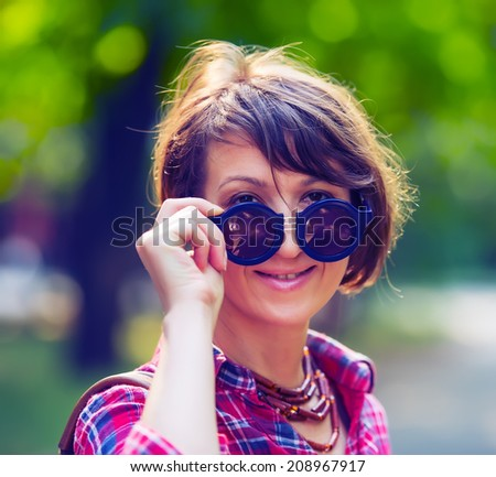portrait of a pretty woman in sunglasses on background of city park, age forty to forty-five years