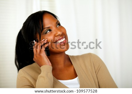 Portrait of a pretty woman looking up while talking on cellphone at home indoor - stock photo