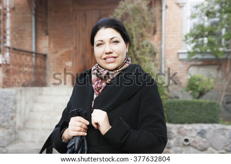 portrait of a pretty woman near the house in autumn