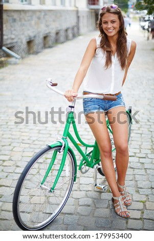 Portrait of a pretty woman on bicycle  - stock photo