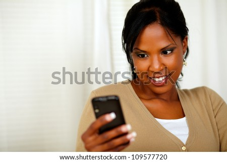 Portrait of a pretty woman reading a text message by the mobile - stock photo