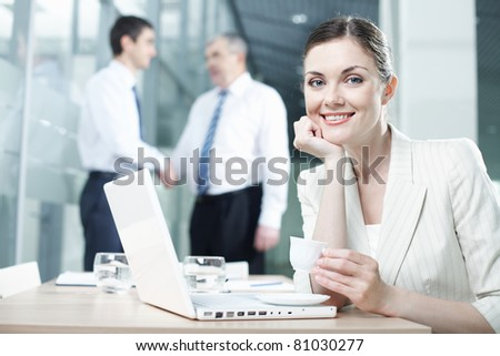 Portrait of a pretty woman sitting at table with laptop - stock photo