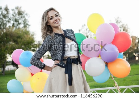 Portrait of a pretty woman standing  in a park against the sunset, outdoors - stock photo
