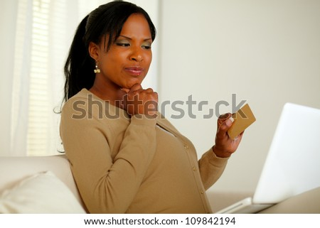 Portrait of a pretty woman thinking whether to buy online with her credit card while sitting on sofa in front her laptop at home indoor - stock photo