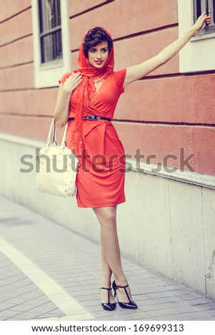 Portrait of a pretty woman, vintage style, in urban background, wearing a red dress
