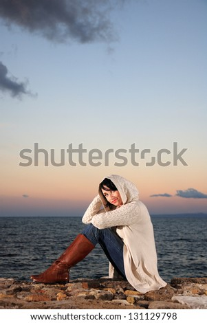 portrait of a pretty woman with knit top by the sea - stock photo