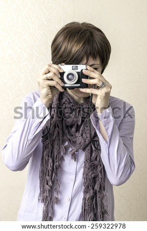 Portrait of a pretty women taking photographs with vintage retro camera
