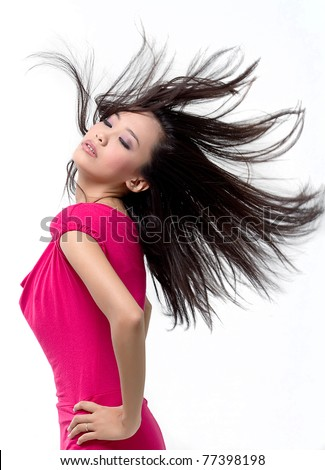 Portrait of a pretty young asian girl with hair lightly fluttering in the wind - stock photo