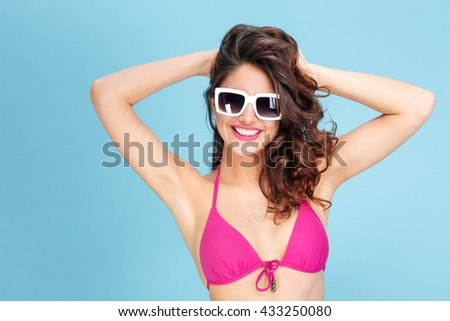 Portrait of a pretty young beach girl wearing sunglasses and swimsuit isolated on the blue background - stock photo