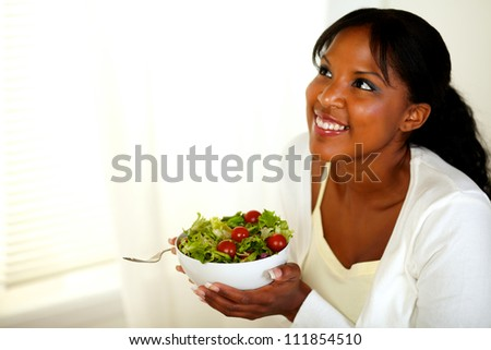 Portrait of a pretty young black lady looking up and smiling while holding a salad. With copyspace. - stock photo
