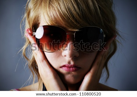 Portrait of a pretty young blond teenager girl with large dark sunglasses, looking sombre, holding her face or covering her ears, over dark grey background