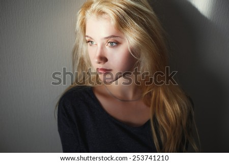Portrait of a pretty young blonde girl sitting near wall inside her room