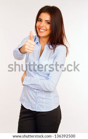 Portrait of a pretty young businesswoman giving you the thumbs up - stock photo