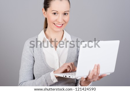 Portrait of a pretty young businesswoman holding a laptop on a gray background